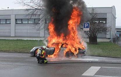 Ein Feuerwehrmann löscht den brennenden Porsche 911 GT3